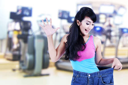Happy asian woman posing in gym with her old big pants photo