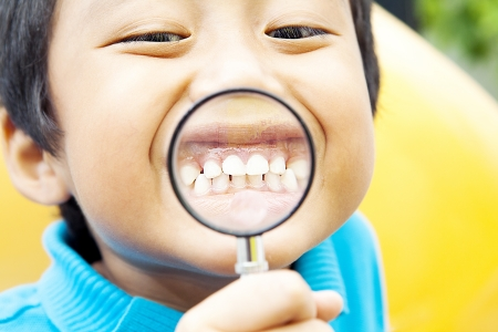 Young asian boy showing his healthy teeth through hand magnifier photo