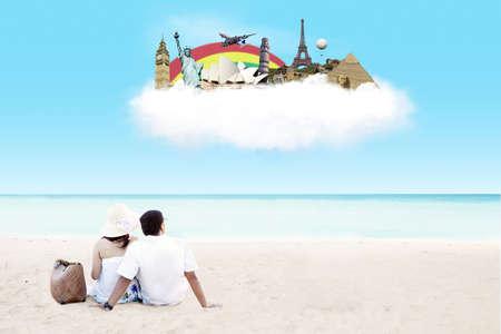 so�ando: Pareja joven sentado en la playa junto con so�ando con destino en la nube Foto de archivo