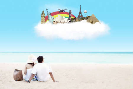 Young couple sitting together on beach with dreaming of travel destination on the cloud photo