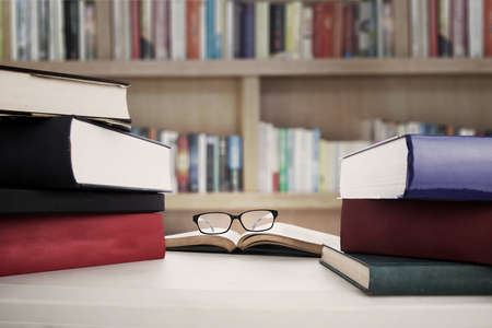 data dictionary: Closeup of reading glasses on the book betwen stack of textbooks. shot in the library Stock Photo