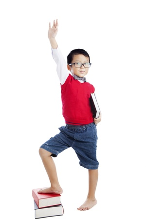 raise hand: Schoolboy with his hand raised ready to answer a question. Isolated on white.