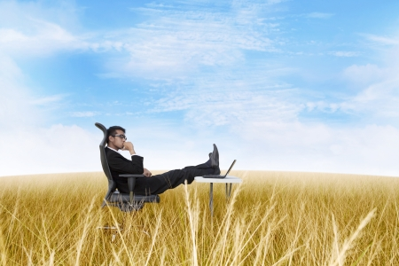 Thoughtful businessman with laptop computer on the field 스톡 콘텐츠