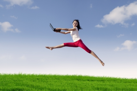 expressing: Portrait of asian woman with laptop jumping in meadow expressing her success