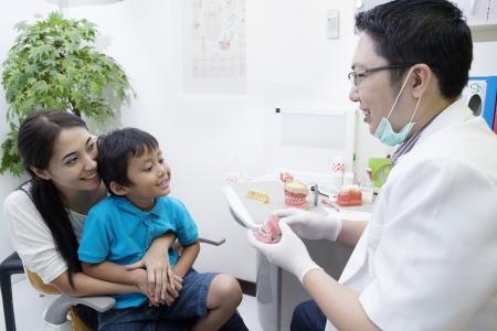 appareil dentaire: Portrait de dentiste mâle montrer un échantillon des accolades à son patient au bureau