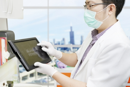 Male dentist pointing at computer tablet to show dental x-ray  shot at the office photo