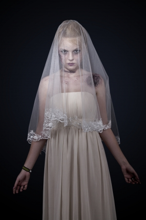 looked: Portrait of zombie bride looked scary and standing at dark background  shot in studio