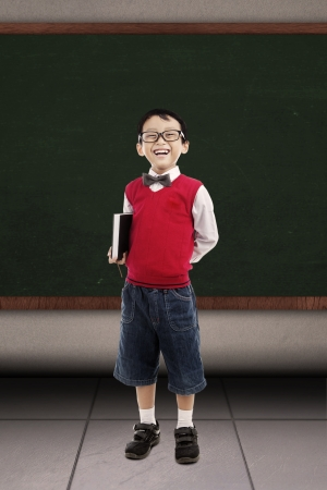 Back to school concept  Smiling elementary school boy holding book and ready for studying Stock Photo - 15165496