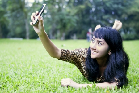 taking photograph: A young asian woman taking her photo by using mobile phone on the meadow