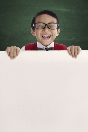 Young asian schoolboy showing blank copy space. shot in the class photo