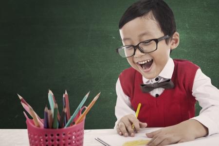 Retrato de feliz estudiante asiático escuela primaria dibujar una imagen utilizando lápices de colores. un disparo en la clase Foto de archivo - 15263982