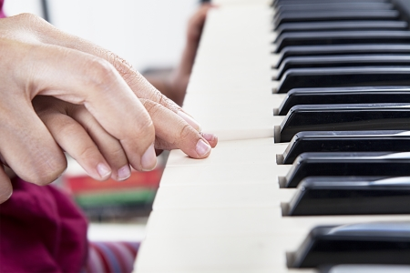 Closeup of hand guiding little piano player playing the piano in the musical class