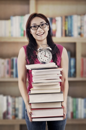 Exams time concept: college student prepares a pile of textbooks and alarm clock for preparing exams photo