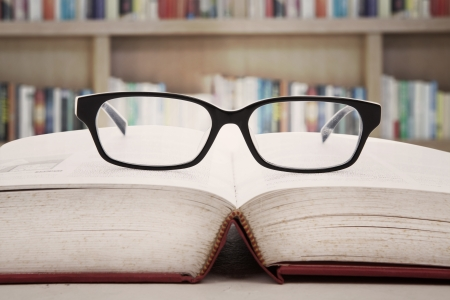 Close-up van een leesbril op het boek. geschoten in de bibliotheek