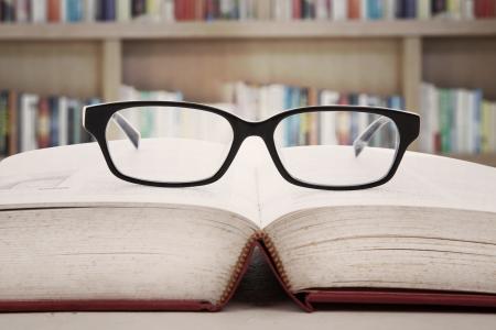 ley: Primer plano de las gafas de lectura sobre el libro. un disparo en la biblioteca