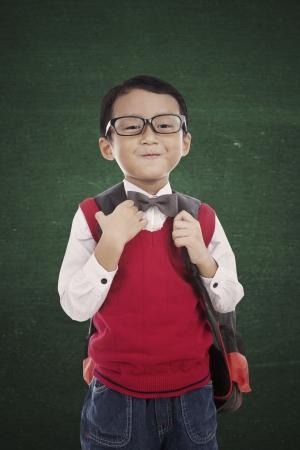 ni�o parado: Retrato de ni�o de 5 a�os de pie en fornt de pizarra y listos para la escuela