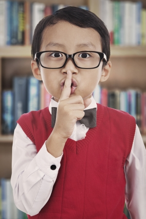 hushing: Cute asian elementary school student with his finger over her mouth, hushing. shot in the library