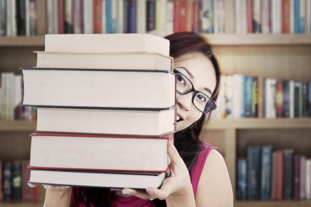 Portrait of female college student smiling behind thick books. shot in the library Stock Photo - 15263976