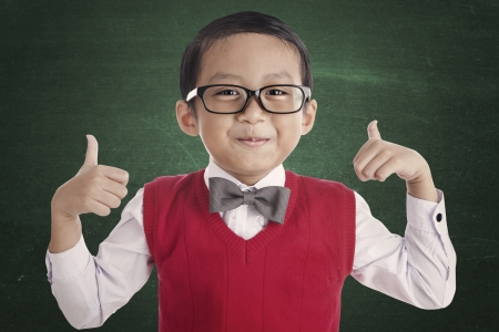 male's thumb: Portrait of asian elementary school student and thumbs-up. shot in the classroom