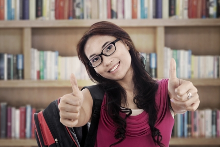 Portrait of asian college student showing thumbs-up. shot in the library photo