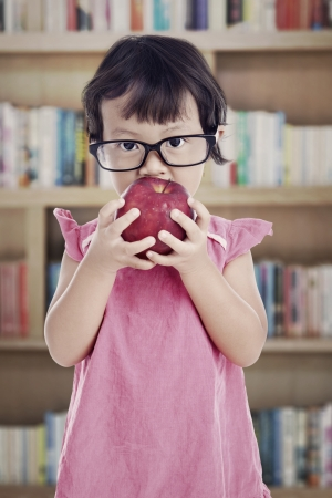 Portrait of female preschooler eating red apple in the library photo