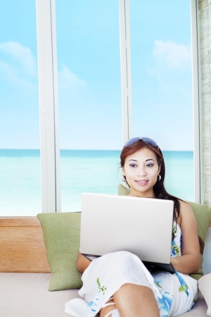 Portrait of beautiful asian woman working on laptop with ocean view on the window photo