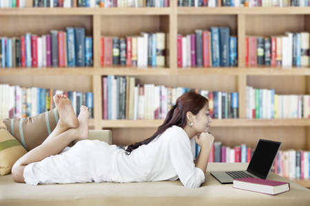 ultrabook: Young asian woman looking at laptop in library with background of books collection on the bookshelf Stock Photo