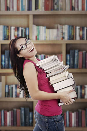 Attractive young female college student carrying a stack of books in the library photo
