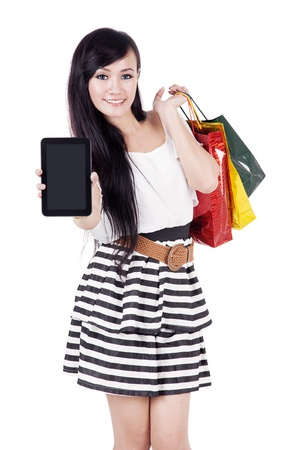 online purchase: Beautiful asian woman showing empty screen of computer tablet while carrying shopping bags