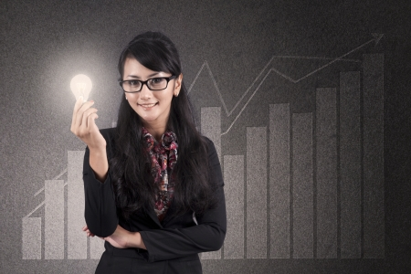 investment solutions: Beautiful asian businesswoman with glasses holds a light bulb over diagram background