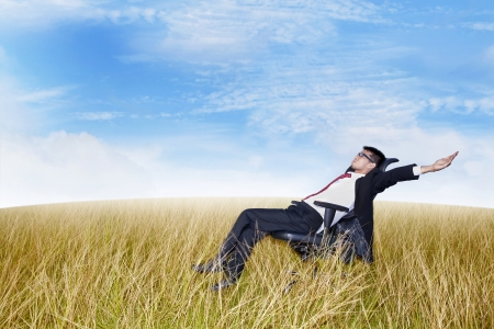 Businessman on his office chair with his arms and feet up in the air. Shot outdoor in marshes Фото со стока