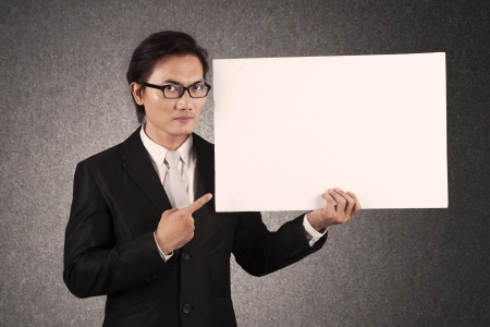Young businessman pointing at an empty copy space. shot in studio photo