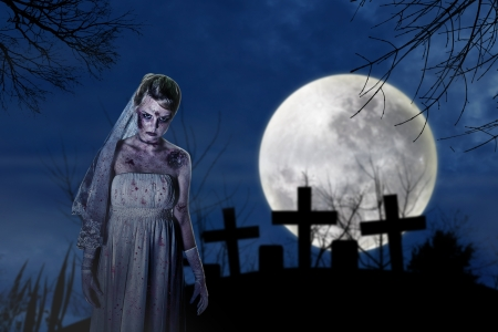 Halloween scene with creepy zombie bride on the dark night at graveyard photo