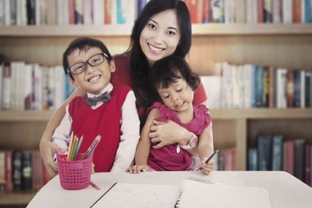 asian teacher: Portrait of smiling young asian mother with her children. shot in the library Stock Photo