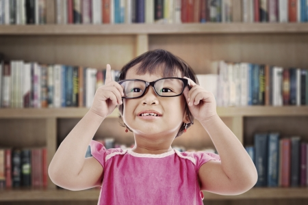 Portrait of asian female preschooler wearing glasses and rises her finger. shot in library photo
