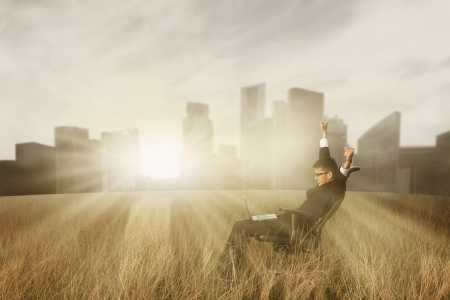 Free successful businessman with laptop in the field photo