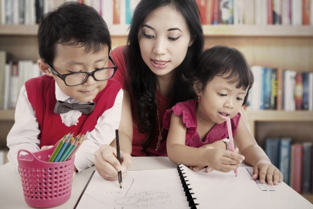 asian teacher: Portrait of young asian mother guiding her children to draw and write on the paper. shot in the library Stock Photo
