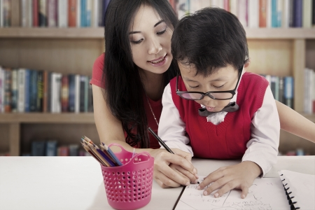 Portrait of elementary school student learn to write with his mother. shot in the library photo
