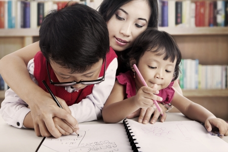 Portrait of young asian children write on the paper with their mother. shot in the library photo