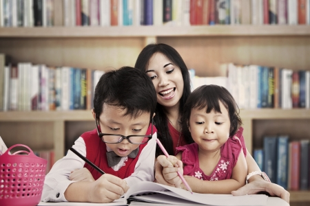 Portrait of young asian mother guiding her children to draw on the paper. shot in the library photo