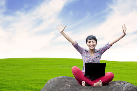 Pretty woman with laptop sitting on the stone under clear sky  Stock Photo - 15390536