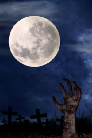 graves: Spooky graveyard with zombie hand coming out of the ground Stock Photo