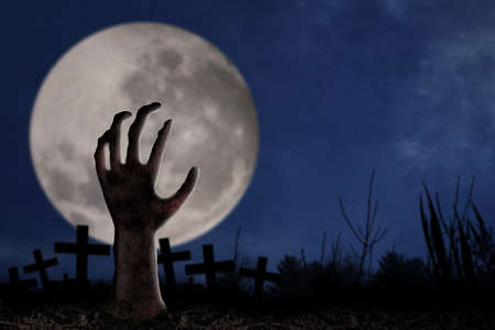 spook: Spooky graveyard with zombie hand coming out of the ground Stock Photo