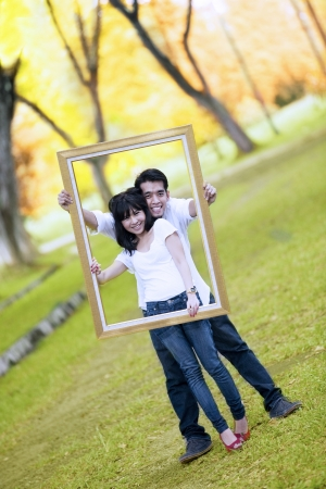 dating and romance: Portrait of young couple holding wooden frame. shout outdoor during autumn