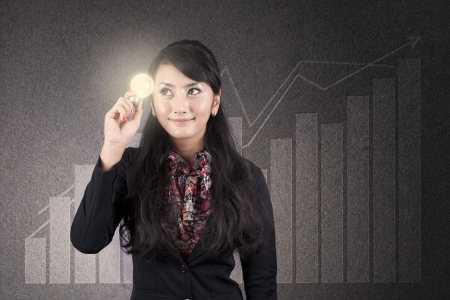 Beautiful asian businesswoman with glasses holds a light bulb over diagram background photo