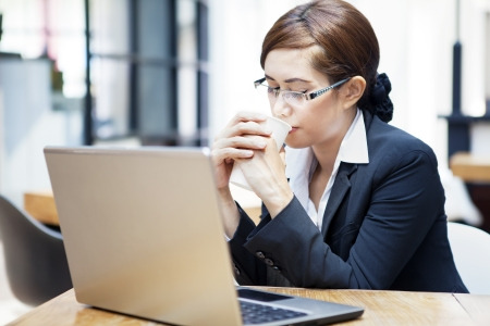 Portrait of young businesswoman with laptop computer drinking coffee at cafe Stock Photo - 15474310