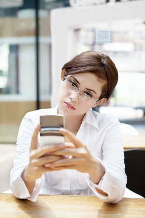 face work: Portrait of beautiful businesswoman typing messages on mobile phone at cafe Stock Photo