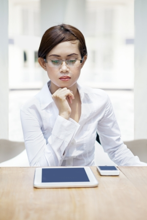 Portrait of businesswoman with mobile devices: digital tablet and mobile phone. shot at cafe Stock Photo - 15474325