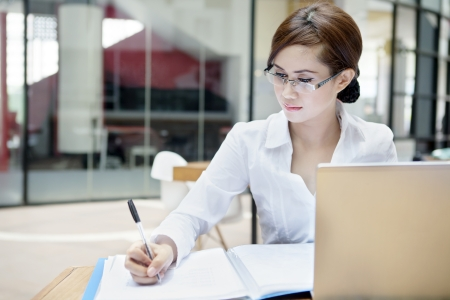 Portrait of businesswoman with laptop writes on a document at her office photo