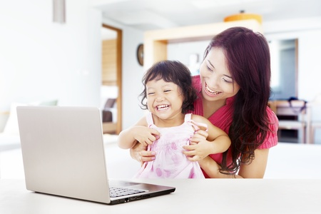 Shot of happy young mother and daughter with ultrabook laptop computer. shot at home photo